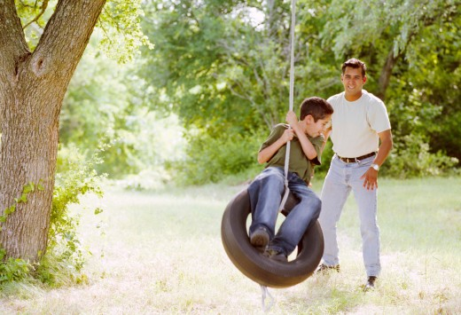 Father Pushing Son on Tire Swing