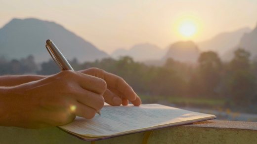 Young woman writing morning pages in diary outdoor, close-up